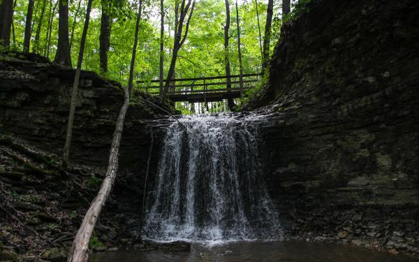 A small bridge crosses over a waterfall at Charlestown State Park.