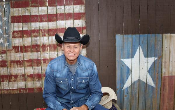Photo of Neal McCoy in front of fence painting with US and Texas flags
