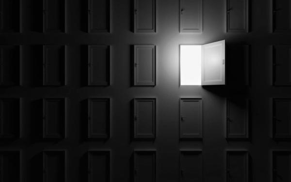 One lit open door on a wall of unopened doors in dark room