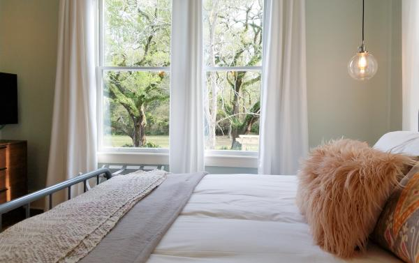 View of a room at Abita Springs Hotel showing a bed with a fluffy pillow and two windows that frame a pair of oak trees outside.