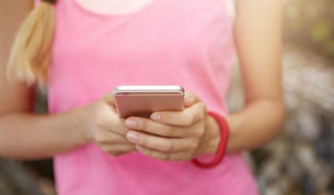 Athletic Woman with Pink top using cell phone