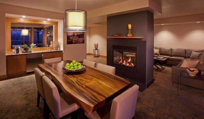 Long wood dining table in front of fireplace in hotel suite
