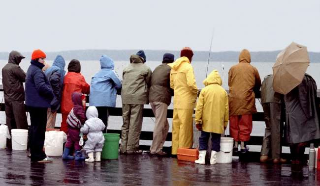 People in rain coats fishing off pier