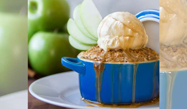 Image of apple cobbler in individual serving with ice cream and caramel on top