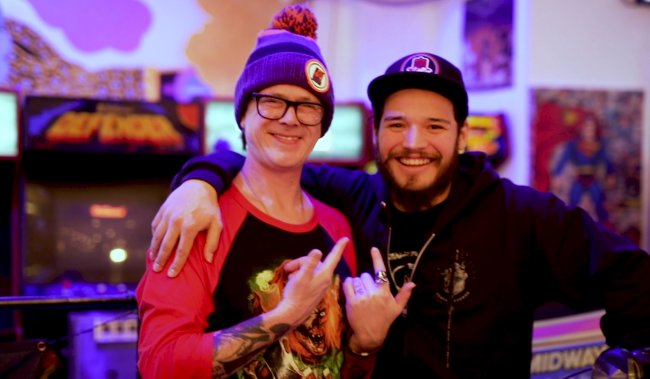 Two men smiling and embracing in front of arcade games