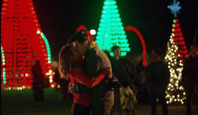 A man and a woman kissing at a Christmas Festival.