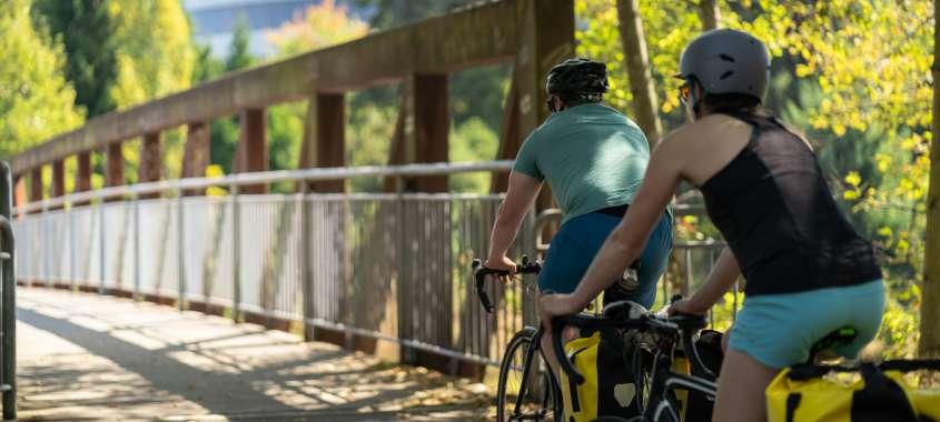 Couple riding bikes across bridge on Interurban Trail in Tukwila