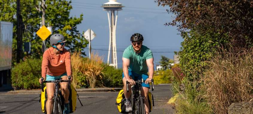 Two bicyclists riding in front of Space needle
