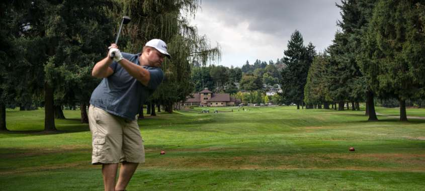 Man Teeing off at Fosters Golf Links in Tukwila