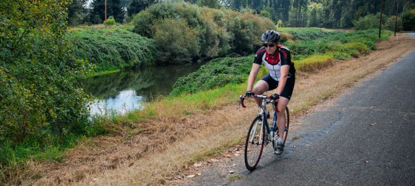 Man Cycling on the Interurban Trail Next to Green River in Seattle Southside