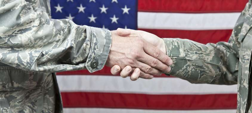 Military Uniformed Men Shaking Hands in Front of American Flag