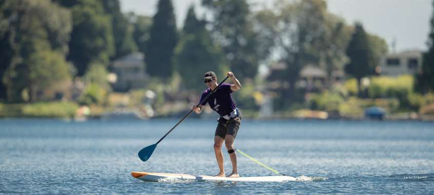 Man on water with oar on stand-up paddle board