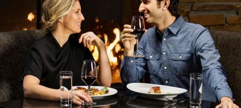 Couple enjoy dinner and wine in front of fireplace