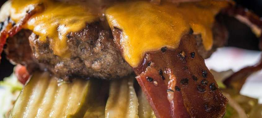 Close up bacon cheeseburger with melted cheese and peppered bacon