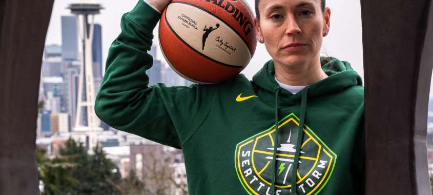 Sue Bird holding a WNBA Basketball overlooking Seattle