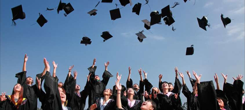 Grads throwing caps into air in celebration