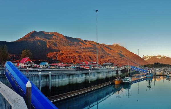 a harbor and a business district in Valdez. Mountains in background
