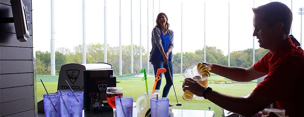 Man pours beer while his Date tees up at Topgolf in Overland Park