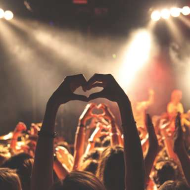 Attendees enjoying a concert in Fayetteville NC, hands up in air forming a heart, showing performers on-stage how they feel about the performance