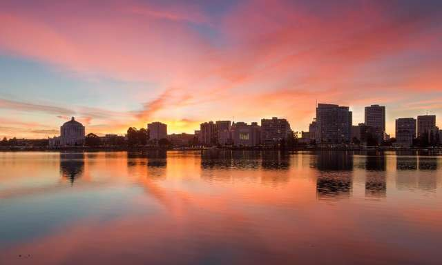 View of Oakland across Lake Merritt at sunset with pink and purple sky
