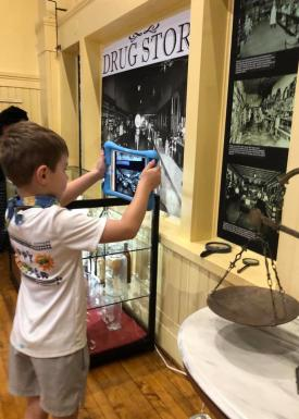 Boy using an iPad to look at a history exhibit