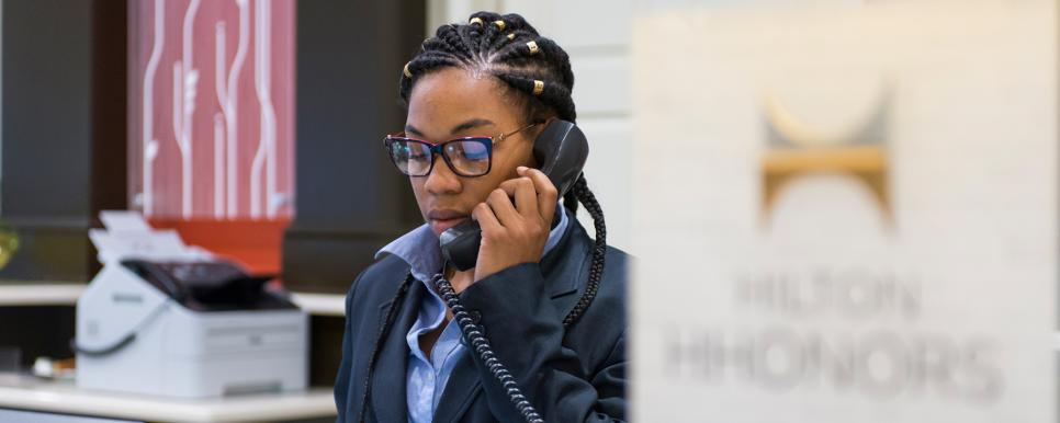 Hotel Front Desk Worker Speaking on a Phone