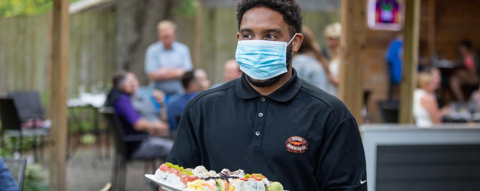 Chiba Server Wearing a Face Mask and Carrying a Plate of Sushi