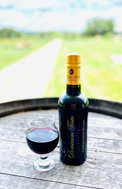 Photo of a bottle of Dominum Tinto Port and Glass on a wine barrel outside of Carter Creek Winery Resort & Spa