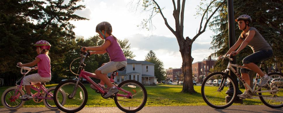 Two young girls and a woman riding bikes on the Monon Trail