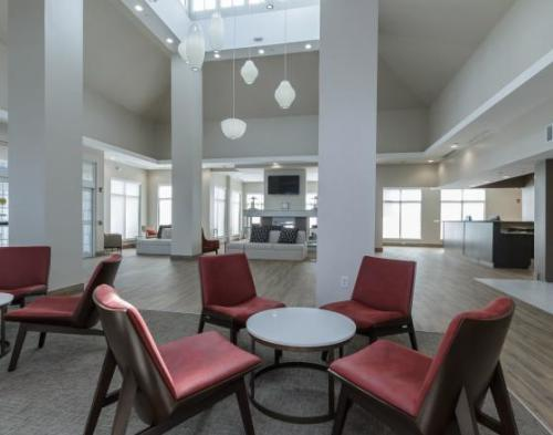 Red chairs around a white table in a white painted lobby at the Hilton Garden Inn Elkhart