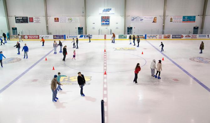A wide view of people skating around the Wichita Ice Center during an open skate session