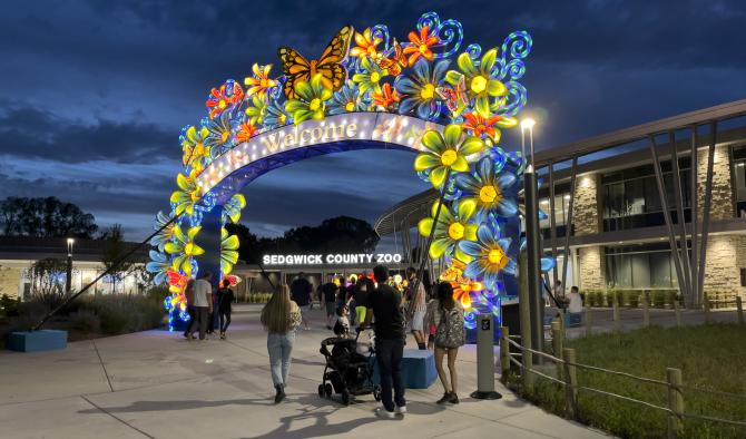 A family with a stroller walks underneath the illuminated entrance of the Sedgwick County Zoo in winter