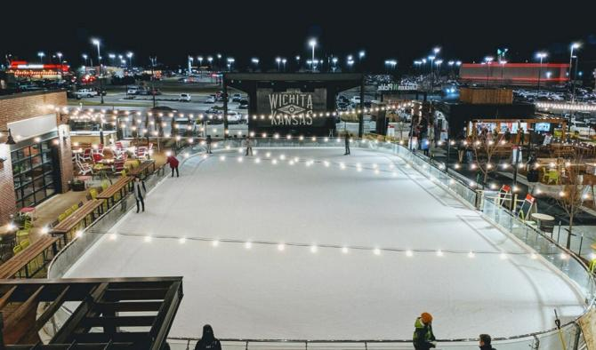 About a dozen people enjoying a nighttime skating session at an outdoor rink in Wichita, KS