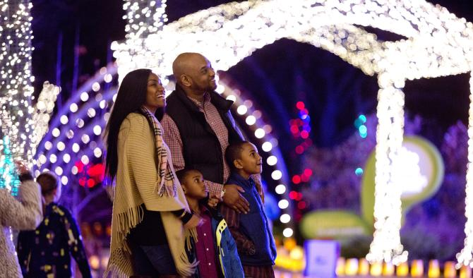 A family of four stops to admire the lights as they walk through a holiday light display during Illuminations at Botanica Wichita
