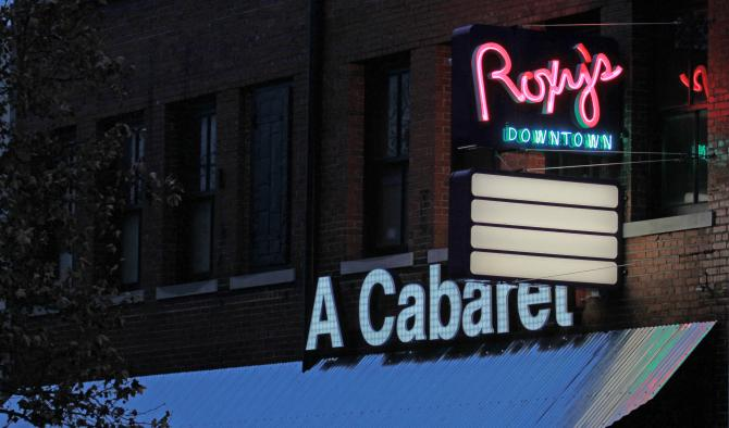 """A pink and blue neon sign that reads """"Roxy's Downtown"""""""