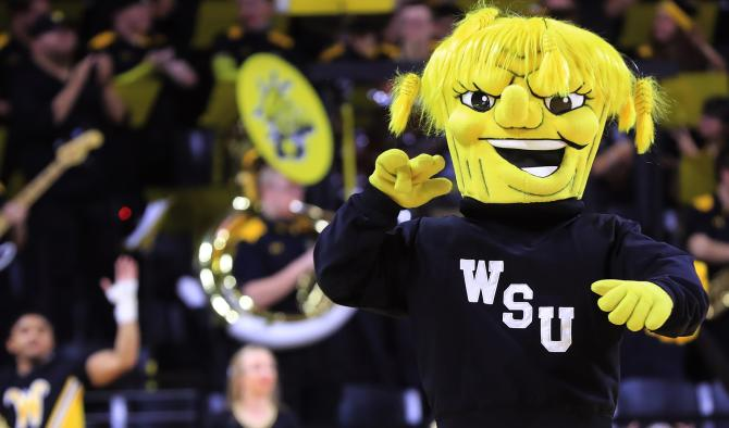 The Wichita State Shockers mascot WuShock walks in front of the school's marching band during a college basketball game.