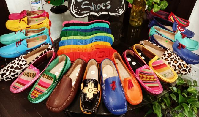 Colorful slip-on shoes arranged in a circle around the outside of a circular glass table
