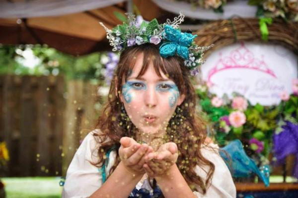 Women dressed as fairy blowing glitter