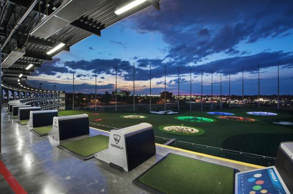 Looking out at lit up targets in an evening sky from the climate controlled tees at Topgolf in Brooklyn Center, MN