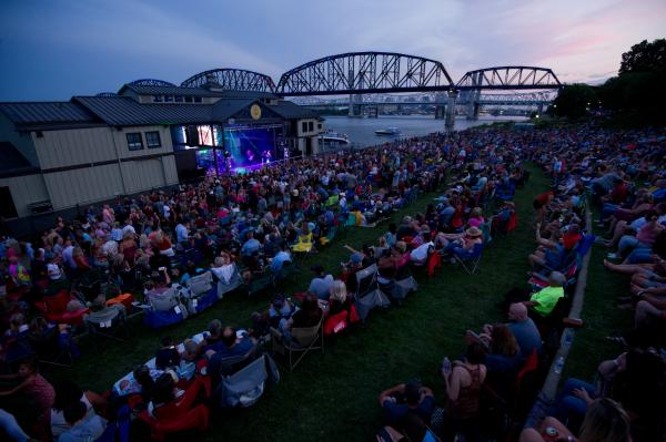 Crowd sitting in lawn chairs at dusk for a show at the Jeffersonville RiverStage