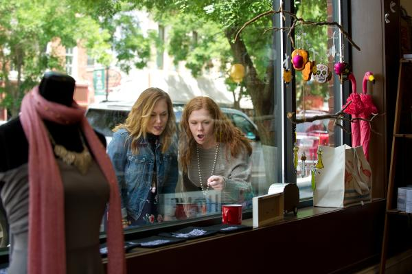 Women looking at goods through a shop window in Downtown New Albany
