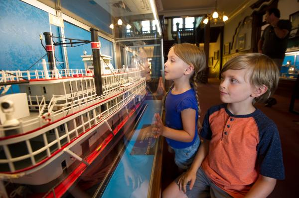 Two kids looking at a boat model structure at the Howard Steamboat Museum
