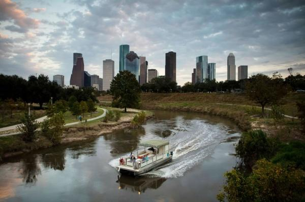 Buffalo Bayou Boat Tour Going down a river with the Houston, TX skyline in the background