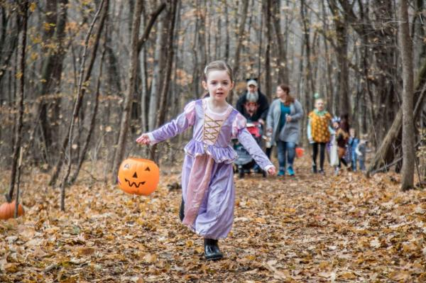 Little girl in princess dress running along a trick-or-treat path in the woods