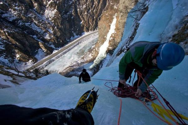 an ice climber looking down at other climbers on a frozen waterfall