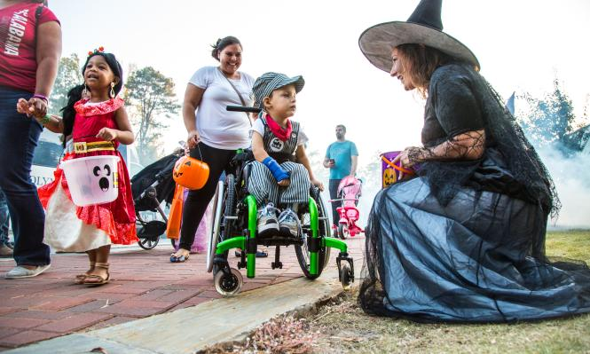 Adorable child in wheelchair with his guardian and Spooky Springs Witch character trick-or-treating.