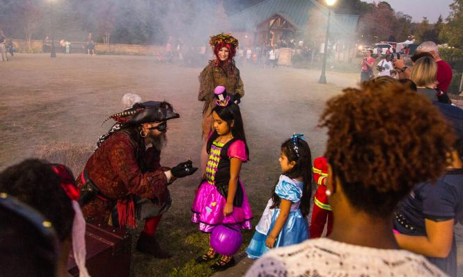 Pirate passing out candy to young trick-or-treaters at Spooky Springs in Sandy Springs
