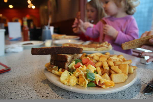 Two little girls eating breakfast at the Village Deli