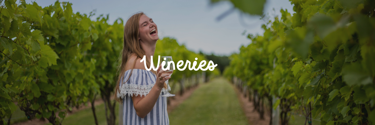 "Girl sipping wine and walking down the aisles of a vineyard with the word ""wineries"" on top of the image"