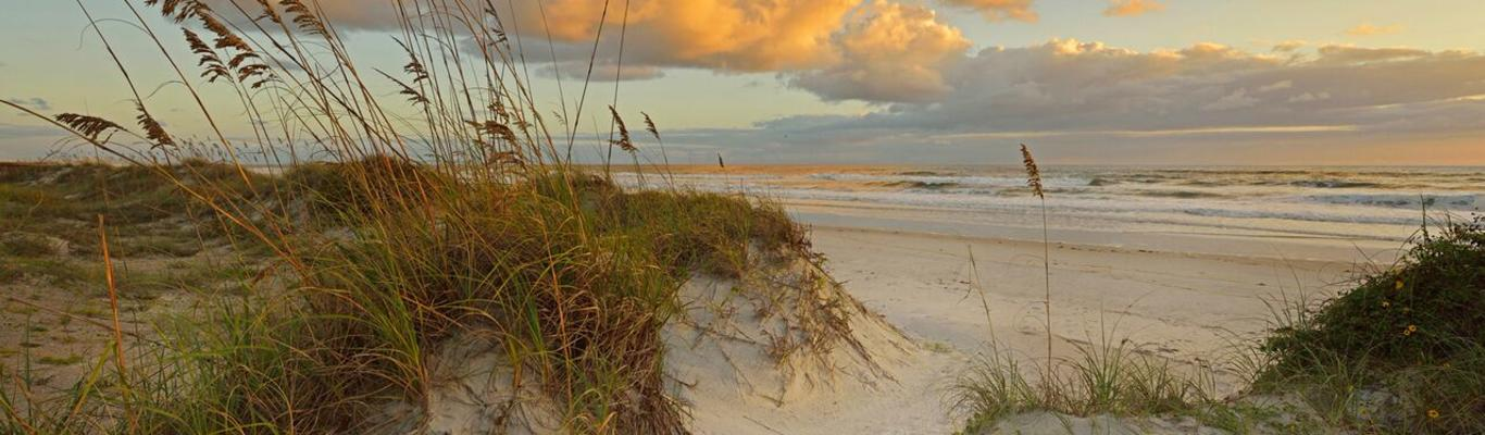 The sun rises over the dunes of Daytona Beach